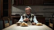 Un anciano sentado en una mesa en la película El abuelo