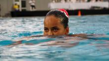 Una joven nadadora compite en una piscina de los Juegos Nacionales.