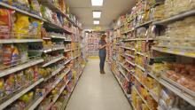 Mujer revisando productos en el pasillo de un supermercado