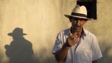 Campesino con sombrero fumando un cigarro. Escena de la película La tierra y la sombra.