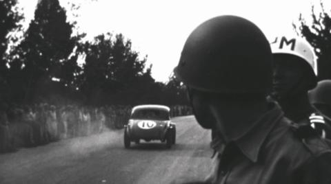 Soldados de la policía militar viendo carreras de autos en los años 60