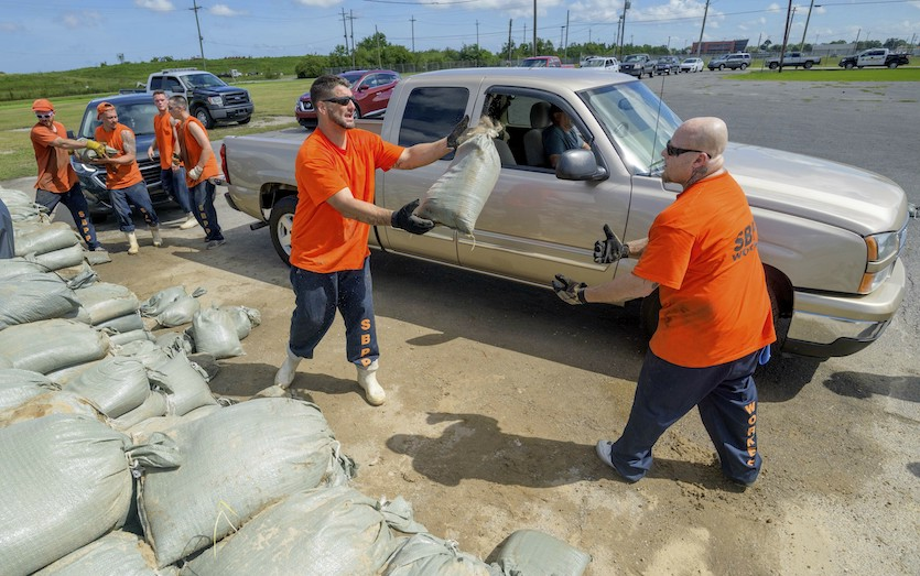 St. Bernard Parish Sheriff's Office inmate workers move free sandbags for residents in Chalmette, La., Thursday, July 11, 2019
