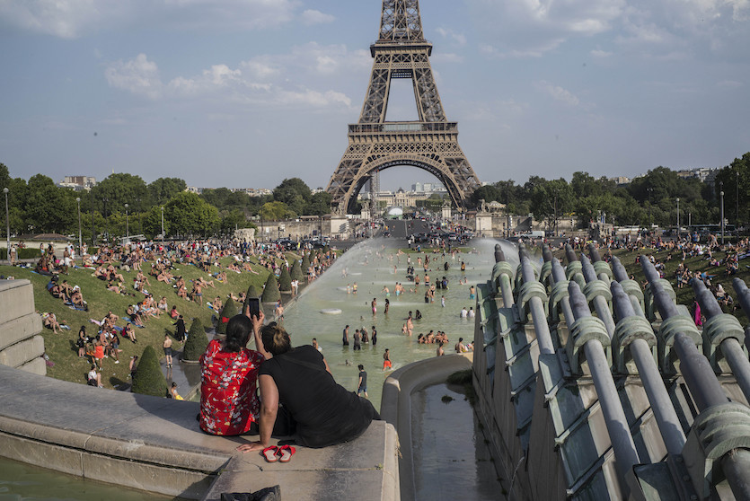People cool down in the fountains of the Trocadero gardens in Paris on Thursday July 25, 2019