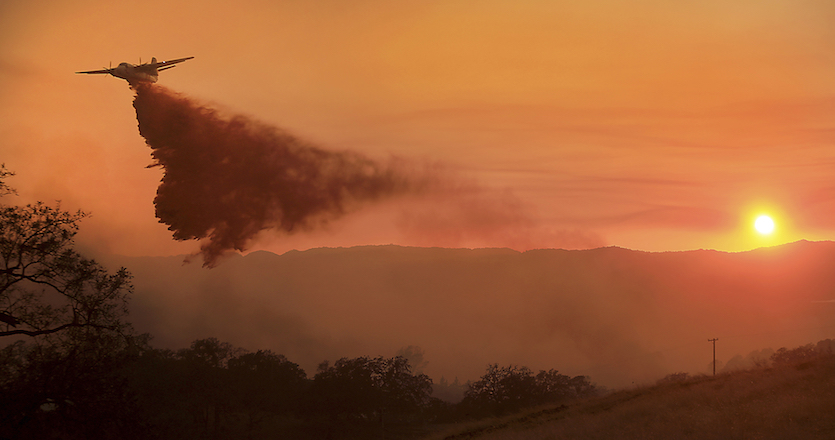 A CalFire air taker makes a drop on a wildfire at sunset as the pilot protects structures on the Hawkeye Ranch above Geyserville, Calif., Thursday Oct. 12, 2017.