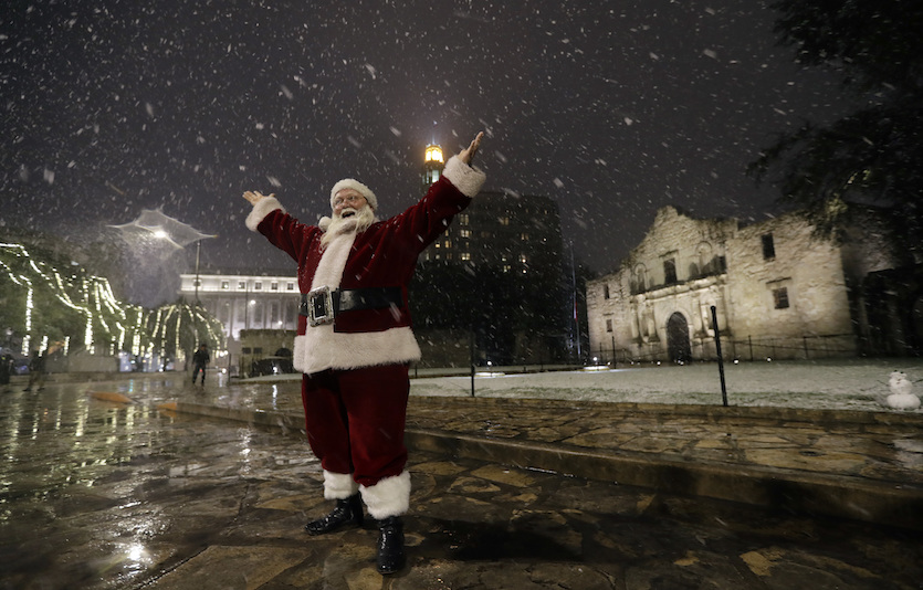 Dressed as Santa Claus, Eldon Hansen stands in front of the Alamo as snow falls in downtown San Antonio, Thursday, Dec. 7, 2017