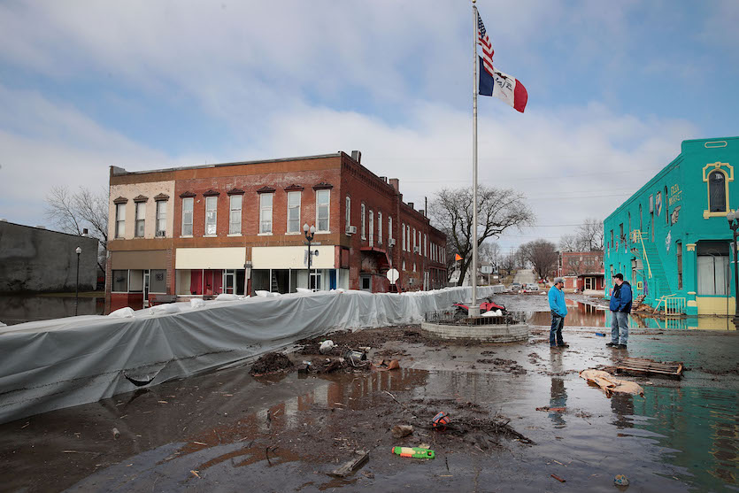 Mud covers a street through downtown Hamburg, Iowa, as flood waters begin to recede on Wednesday, March 20, 2019