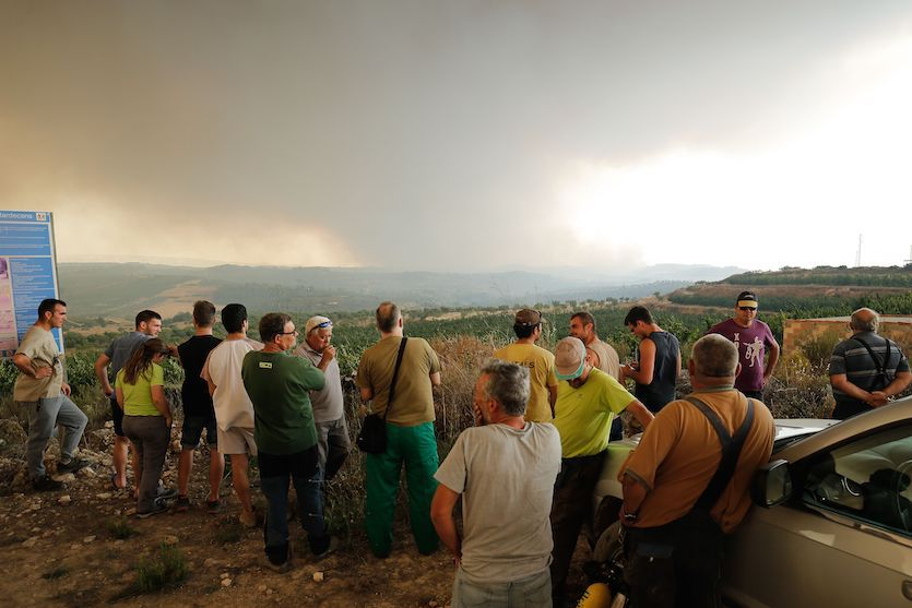 Residents gather to observe a forest fire raging near Maials in the northeastern region of Catalonia, Spain, on June 27, 2019