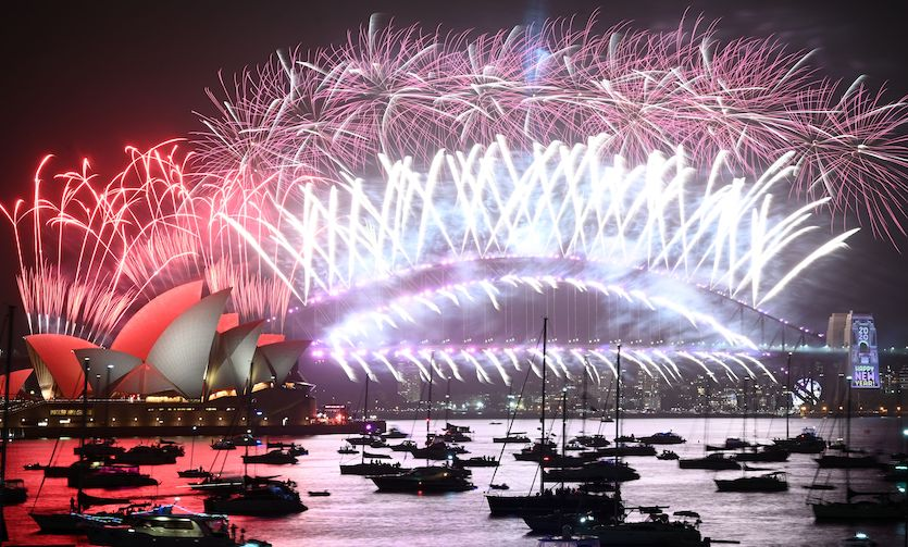New Year's Eve fireworks erupt over Sydney's iconic Harbour Bridge and Opera House (left) during the fireworks show on 1/1/20