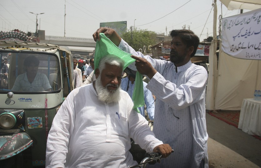 Using wet towels to cool people in Karachi, Pakistan, 4/22/2018