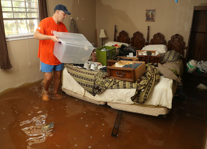 Denny Lazarus helps salvage what he can from his parents' flooded home on August 18, 2016 in St. Amant, Louisiana