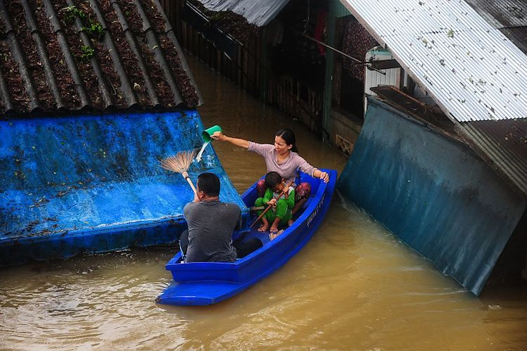 A family escapes floodwaters in southern Thailand on Jan. 2, 2017