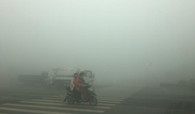 Motorcyclists ride through thick smog on January 9, 2017, in Zhengzhou, China.