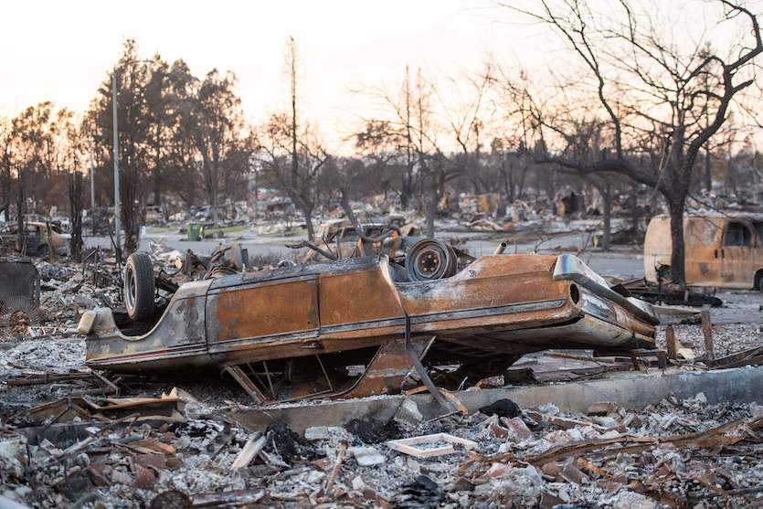 A flipped, burned-out car sits among debris and rubble in a fire-destroyed neighborhood in Santa Rosa, California on Oct. 20, 2017