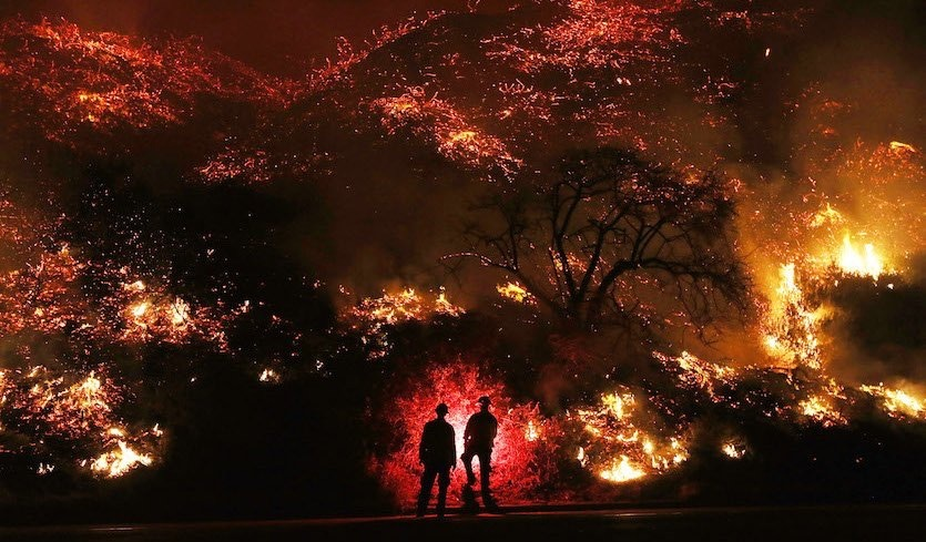 Firefighters monitor a section of the Thomas Fire along U.S. Highway 101 northwest of Ventura, California, in the predawn hours on Thursday, December 7, 2017