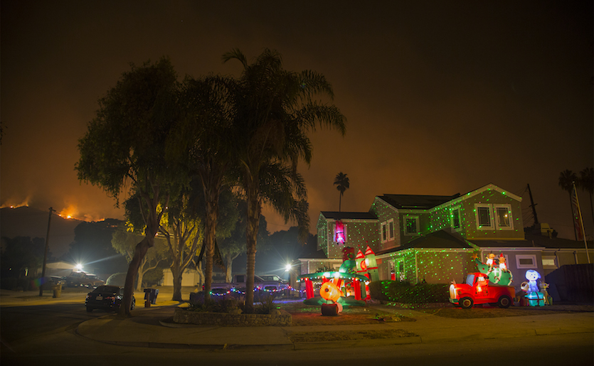 Christmas decorations illuminated a house in Carpinteria, Calif., on Sunday, December 10, 2017, as the growing Thomas Fire advanced toward seaside communities in Santa Barbara County