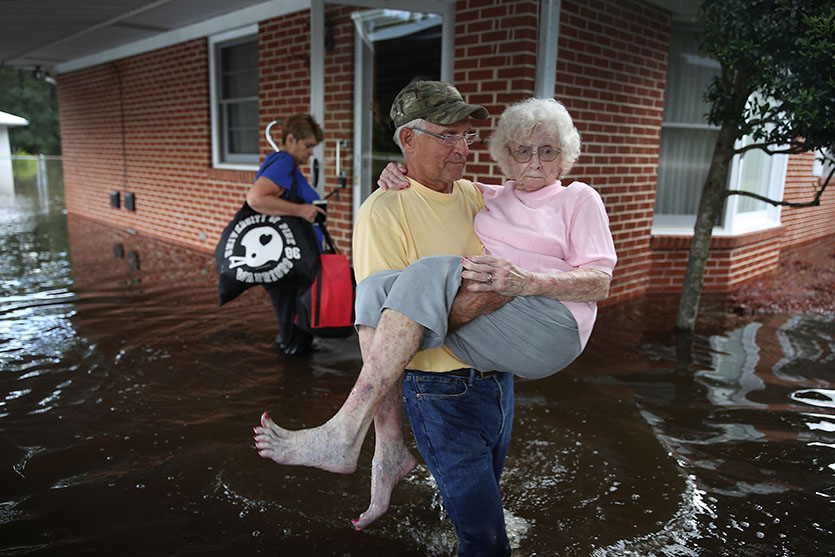 Bob Richling carries Iris Darden as water from the Little River starts to seep into her home on September 17, 2018, in Spring Lake, North Carolina