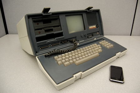 An Osborne Executive portable computer, from 1982, and an iPhone, released 2007. The Executive weighs 100 times as much, has nearly 500 times the volume, cost 10 times as much, and has a 100th the processing power of the iPhone.