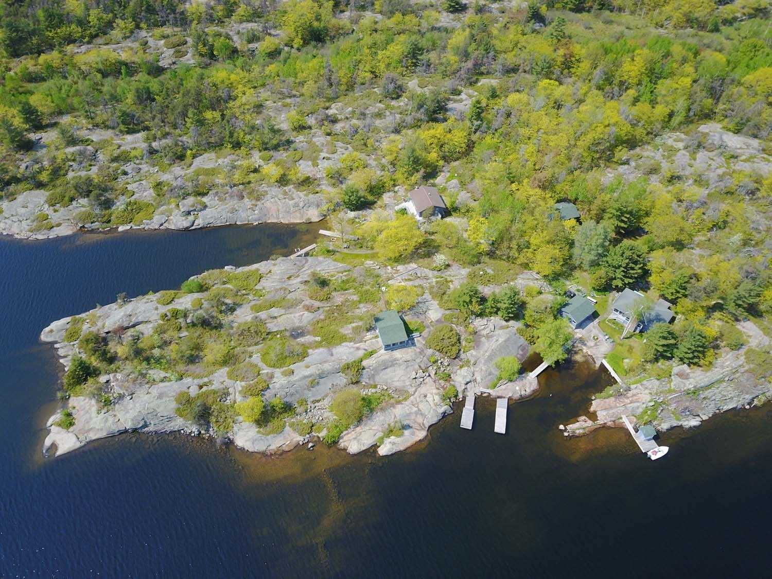 10 Ac In Pointe Au Baril's Georgian Bay Freshwater Granite & Pines Island Community, 900' Frontage, 2 Coves & Private Back Bay. Spectacular West, East & South Views. Surrounded By Undevelopable Natural State Lands. 3 Main Cottages W/ Full Kitchens, Baths & Privacy + 2 Cabins W/ Kitchenettes. 10 Bdrms, Workshop W/ Concrete Floor. Marine Storage Building On The Front Wharf, Floating Docks, Hydro, Some Baseboard Heat, 2 F/P's & Wood Stove In The Cottages.