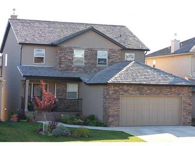 It is my pleasure to represent this gem in Royal Oak Estates. The main floor boasts red oak hardwood, tile and carpet flooring, a formal dining room, a den with French doors, vaulted ceilings and a glorious kitchen equipped with stainless steel appliances, granite countertops and maple cabinets in a rich coloured stain.  Off the nook is your sunny south backing no maintenance duradeck where you can sit back and enjoy the mountain views.  The upper level has three bedrooms incl. a master retreat with a 5pc ensuite. The walkout level contains a wet bar, granite island, a bar fridge, a 2nd fireplace with stonework to the ceiling, a 4th bedroom, a 4pc bath with heated floors and a steam shower. Outside the lower level, the landscaped back yard has a beautiful stamped concrete pad. There is also a gas connection in the concrete for an outdoor gas firepit.  With a new school, close proximity to Royal Oak and Beacon Hill shopping centres and Stoney Trail, you will not be disappointed.  Call today!