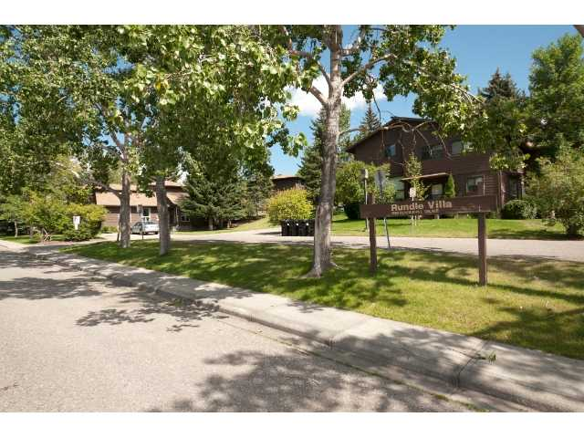 Surrounded by schools, park-space, and mature Spruce trees, this quiet well-managed complex feels like an oasis in the city.  Within walking distance of the C-train and first 2 levels of both the public and private schools, and close to all shopping and the Peter Lougheed Hospital.  This unit has had the same caring owner for 20 years and it shows.  Upstairs are 3 decent-sized bedrooms -- the master with its own 2 piece ensuite and walk-in closet -- new carpeting, and a nicely renovated main bath with heated floor tiles.  New lighting, newer appliances and extra attic insulation also add value. The fireplace and real hardwood on the open main level complement the private balcony, giving a cabin-like feel.  The basement sets this home apart with loads of professional built-in cupboards and shelving providing plenty of tidy storage.  The tucked-in fridge, plus counter and sink help with the goodies when watching the big game or your favorite movie.  Come see for yourself.