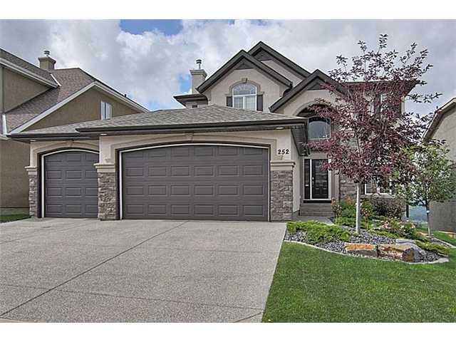 VIEWS-Incredible views of the Mountains and Griffith Woods from this gorgeous ridge home with TRIPLE GARAGE in a quiet cul-de-sac location. This SOUTH WALKOUT is perfect for both family life and entertaining.  The main floor features hardwood flooring, expansive kitchen cabinetry with o/sized island, s.steel appliances w/GAS cooktop and living area with custom cast concrete fireplace and balcony-all with beautiful vistas of the Rockies. A formal dining room and den complete the main floor. The second floor reveals the master suite with double doors and ensuite and two more generously sized bedrooms.  The f-fin WALKOUT basement features a large family/games area complete with wet bar, d/washer and fridge for your convenience.  A king size 4th bdrm and bathroom are perfect for your nanny or teen. With numerous thoughtful features including Hunter Douglas blinds, built-in speakers, 2 furnaces and 2 AIR COND. for your comfort and 2nd vacuflo/faucets in the garage, this home is ready to move into.