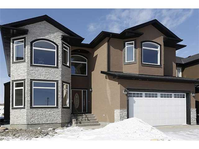 A  BEAUTIFUL  2 STOREY  BRAND  NEW  HOME  IN  ESTSTE  COMMUNITY  OF  KINNIBURGH  IN  CHESTERMERE. MORE  THAN 3000  SQ.  FEET  ON  TWO  LEVELS + FULLY  FINISHED   BASEMENT  WITH  2  BEDROOMS, BATHROOM, SUMMER  KITCHEN/ WET  BAR  AND  HUGE  REC  ROOM. THIS  HOUSE  OFFERS  A  LOT  OF  UPGRADES.  MAIN  FLOOR  OFFERS  LIVING  ROOM,  DINING  ROOM,  DEN,  BEAUTIFUL  KITCHEN  WITH  STAINLESS  STEEL  APPLIANCES,  A  LARGE  FAMILY  ROOM  WITH  BUILT-INS  &  FIREPLACE  AND  A  HUGE  DECK. BEAUTIFUL  STAIRCASE  GO  TO  UPSTAIRS,  OFFERS  SPACIOUS  THREE  BEDROOMS  AND  A  BONUS  ROOM.  MASTER  BEDROOM  HAS  A  5 PIECE  ENSUITE  AND  A  BIG  WALK-IN  CLOSET.  DBL  FRONT  GARAGE  IS  INSULATED  AND  DRYWALLED. HOUSE  COMES  WITH   ALL  STAINLESS  STEEL  APPLIANCES. THIS  COMUNITY  HAS  NEW  K - 9  SCHOOL  AND  HEALTH  CENTRE. 25  MINUTS  DRIVE  TO  DOWNTOWN  OR  AIRPORT.