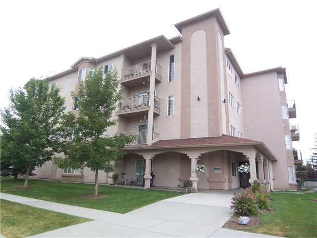SUPER apartment within walking distance to downtown Okotoks. IMMACULATE CORNER UNIT boasting open great room loaded with windows, hardwood floors and gas fireplace. Bright and Cheery kitchen offers white cabinetry and breakfast bar. Master bedroom features 4-piece ensuite.  There are an additional 2 bedrooms and full bath. Patio doors lead to south facing balcony. Separate storage agea. This wonderful well-kept apartment is well worth viewing.