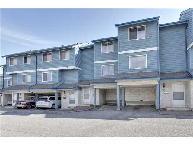 BRAND NEW CARPETS AND LINO was completed Nov 1st.  Affordable starter home in well-managed complex close to all important amenities.  Couple minutes walk to shopping, Peter Lougheed Hospital and to the C-train bringing you quickly to downtown and beyond.  Pets OK with board approval, and lots of visitor parking in addition to your own carport. Large eat-in kitchen, and 14' ceiling and corner fireplace in cozy living room.  Two large bedrooms -- the master has a walk-in closet -- and the bathroom just received NEW TILES AROUND THE TUB.  Patio doors open to your own small backyard, and beyond this is a large common green space.  Quick possession, available immediately.  Quit renting, move right in! MOTIVATED SELLER.