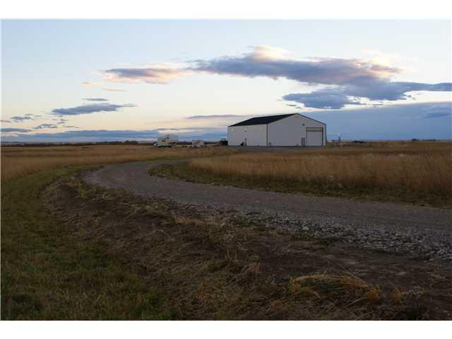 CALLING ALL TRUCKERS/EQUIPMENT OWNERS!!FANTASTIC OPPORTUNITY FOR A GREAT PRICE! LIKE BRAND NEW (only 2yrs old) 5800+ SQ FT SHOP JUST OFF OF HIGHWAY 22X & HIGHWAY 24 ONLY 15 MINUTES TO CALGARY,STRATHMORE OR LANGDON.THIS 104X56 INDUSTRIAL METAL BUILDING(WITH MEZZANINE) HAS HAD NO EXPENSES SPARED AND HAS BEEN WELL CARED FOR AND IS COMPLETE WITH 18FT CEILINGS. PROFESSIONALLY BUILT WITH ALL APPROPRIATE PERMITS.PROPERTY IS CURRENTLY ZONED AGRICULTURAL GENERAL & IS READY TO BUILD YOUR DREAM HOME COMPLETE WITH MOUNTAIN VIEW. Fully serviced with over 2000 Spruce trees planted , lots of gravel parking and professionally built road. Has a drilled 220ft deep water well with 15 GPM Along with gas and power supply lines ready for your new home. The storage is absolutely fabulous and extremely efficient:  it is heated, insulated and good for trucks, any agricultural equipment or just a  fantastic workshop. Flooring: 35 pilings,6ft deep, 7inch concrete bed; ceiling: 15 inch insulated;(2)16ft rollup insulated doors.