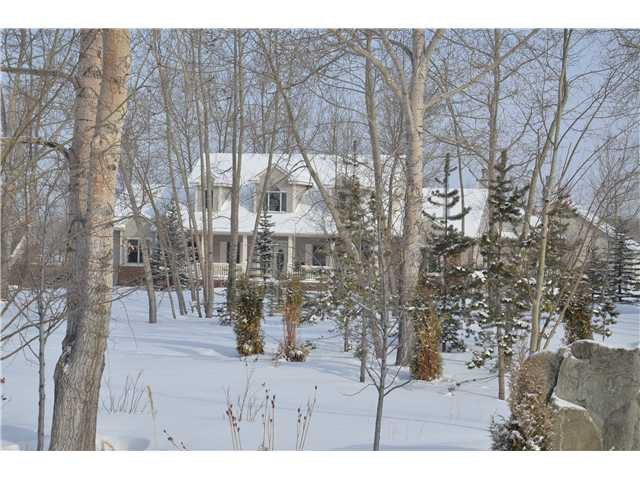 WOW THIS IS THE ACREAGE YOU HAVE BEEN WAITING FOR. FANTASTIC HOME over 5000 sq. ft. fully developed with the master suite on the main floor featuring sitting area with 3-way gas fireplace, luxury ensuite with his/hers walk-in closets. DYNAMITE KITCHEN, hardwood floors, GRANITE COUNTERTOPS, Maple cabinetry, Unique Sitting room, Massive family room loaded with windows for natural lighting  and  wood burning freestanding fireplace. Formal living and dining rooms. Central turned staircase  boasting hardwood treads up to 2 huge bedrooms featuring jack-and-jill bathroom.  Professionally developed lower level with a huge rec room, 2 bedrooms, den, full bath and storage area.  Super huge three-car garage. AND FOR THE MAN OF THE HOME AN ABSOLUTELY SUPER WORKSHOP 2160 SQ. FT. FEATURING FULL BATH, 14 FT CEILINGS AND 3 - 12 FT DOORS, HEATED. UNBELIEVABLE LOT  SUPERBLY LANDSCAPED AND BOASTING MATURE TREES AND A UNIQUE VERY PRIVATE OUTDOOR POOL AREA.  ALL ON 4.88 ACRES.  Approximately 10 minutes SW of Calgary.