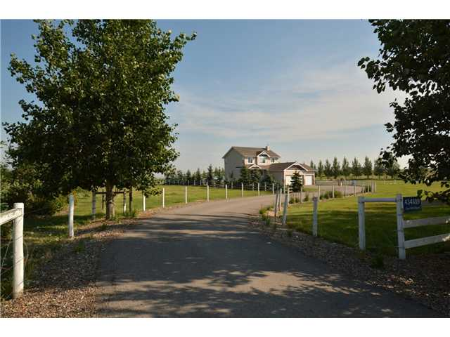 BRING YOUR HORSES & MOVE RIGHT IN TO THIS PICTURE PERFECT ACREAGE ON 3.61 ACRES CLOSE TO OKOTOKS. This 4 bdrm 3 car heated garage home enjoys mtn & ravine views.Love the warmth of the new hand scraped hardwood floors on the main. The kitchen has maple cabinetry ,stainless steel appliances, giant walk through pantry, island eating bar & a sunny breakfast nook. The family room with corner gas fireplace has views out both large picture windows. The front room is a dining room or a home office. The heated cedar sunroom with sky light above the hot tub to watch the stars. Upstairs find two large bdrms & a master retreat with spa like 4 piece ensuite with a soaker tub.The walk up basement has tons of windows, a big bedroom, a generous family room & a 3 pce bath with fabulous fully tiled shower. The 30/36 shop or barn has four stalls, tack room & work shop. Set up with an emergency generator hook up, Training round pen, fenced & cross fenced.  Road access is paved & the paved driveway has a great turn around.