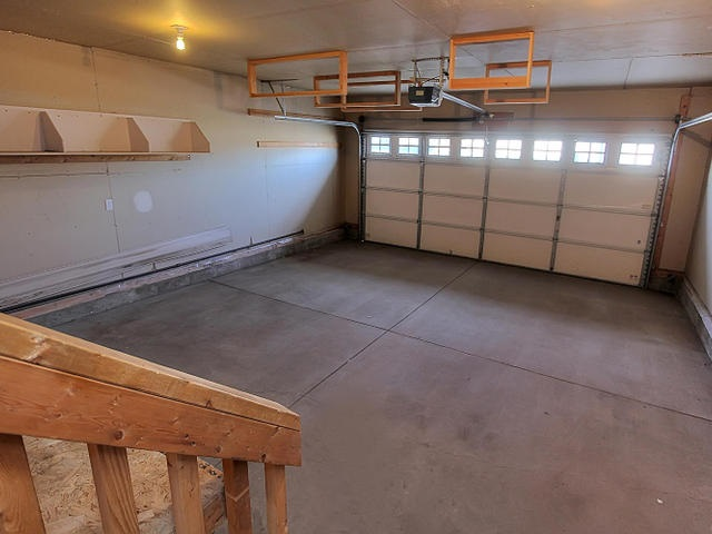 The double attached garage is insulated and drywalled and has attached storage shelving and a work bench.