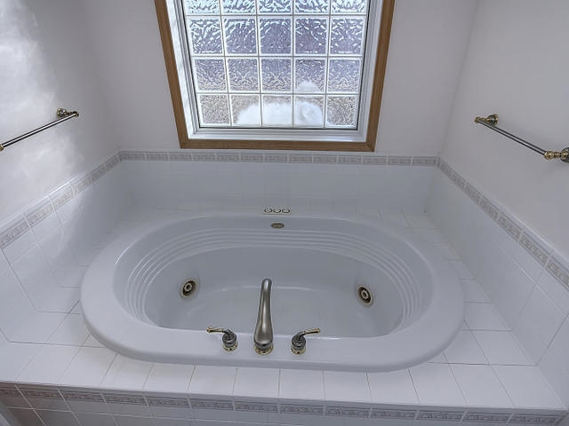 The luxurious extra large and extra deep JACUZZI tub has light over it. The glass block window is being replaced with a privacy window.