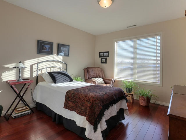 The second bedroom is also large and sunny. The same hardwood is found here and the same neutral paint.