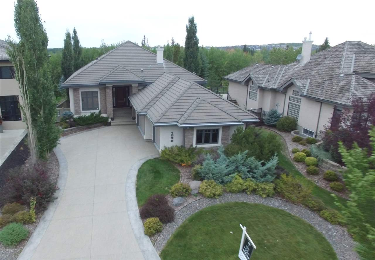 Built by Birkholz Homes on Whitemud Creek Ravine, sits this gorgeous custom 2120 sqft walkout bungalow w/ triple car heated garage. Bright main floor living room features 12? beamed ceiling w/ crown moulding, floor to ceiling windows, gas f/p with floor to ceiling stone & Cabeza de Mono hardwood flooring. An open gourmet kitchen offers solid cherry wood cabinets, butcher block island, built-in S/S appliances, granite countertops & breakfast nook w/ access to the back deck. A spacious main floor master bedroom offers a luxurious 5pce ensuite w/ soaker tub & separate glass shower, W/I closet & private access to the back deck. A laundry/mud room, office & half bath completes the main floor. Descend the spiral staircase w/ curved stone wall to the fully finished basement w/ theatre room, family room w/ stone surround gas f/p, wetbar, games room w/ French door access to the covered patio & professionally landscaped backyard. 3 addt?l bedrooms and Jack & Jill full bath offer plenty of room for a growing family.
