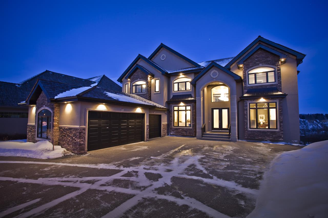 Showcasing the unprecedented views of the North Saskatchewan River & the City Skyline, this stunning 2 storey estate has over 7,500 sq.ft. of living space on 3 floors, and is located on a quiet cul-de-sac in exclusive Wolf Willow Ridge bordered by the River Valley, Wolf Willow Ravine and the Edmonton Golf & Country Club. The sun room & family room are adjacent to the great room boasting a 20' ceiling, floor to ceiling gas f/p, a wall of windows & is open to the gourmet kitchen w/ built-in S/S appliances, granite island w/ breakfast bar & nook w/ balcony access to enjoy the panoramic views. Ascend the dramatic sweeping staircase to the upper level offering 3 large bedrooms with ensuites & the master suite featuring a spacious W/I closet, gorgeous spa-like ensuite & private balcony. The walk-out lower level boasts a large family room w/ a fully equipped wet bar, wine cellar, 10-seat theatre room, home gym and 3 bedrooms w/ ensuites. Meticulous landscaping & almost every room overlooking the River Valley!