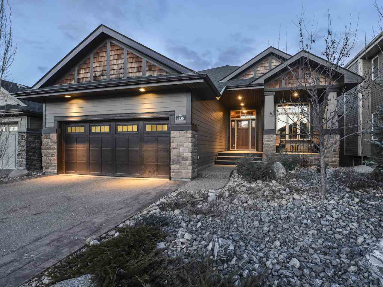 Exquisite 1,811 sq.ft. bungalow with extensive stonework in beautiful Windermere! This former show home built by Hillview Homes has more than one could imagine & the moment you walk thru the front door you feel like you?re home. A bright, open main floor boasts a living room with floor-to-ceiling stone gas f/p, coffered ceiling & expansive windows overlooking the maintenance free backyard & community pond. Opening to a spectacular gourmet kitchen with built-in S/S appliances, oversized island, walk-thru pantry, and breakfast nook with access to the back deck. Main floor living is at it?s best with an impressive den with custom ceiling & built-in bookcase, and a master suite with relaxing 5 piece ensuite including a free standing soaker tub and custom glass shower. Descend the curved staircase to the warm & welcoming walk-out lower level featuring a spacious rec room with double sided f/p, wet bar & 2 addt?l bedrooms. Relax on the beautiful patio or enjoy an evening under the stars around the fireplace.