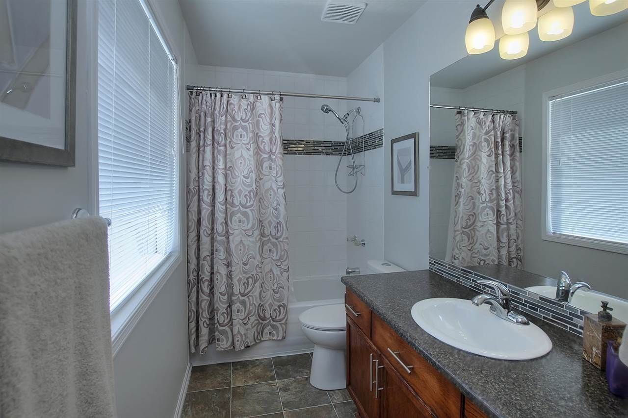 The Master en suite bathroom is spacious with a long vanity, a full window for natural light and built in shelving to store the linens you don't keep in the hallway linen closet.