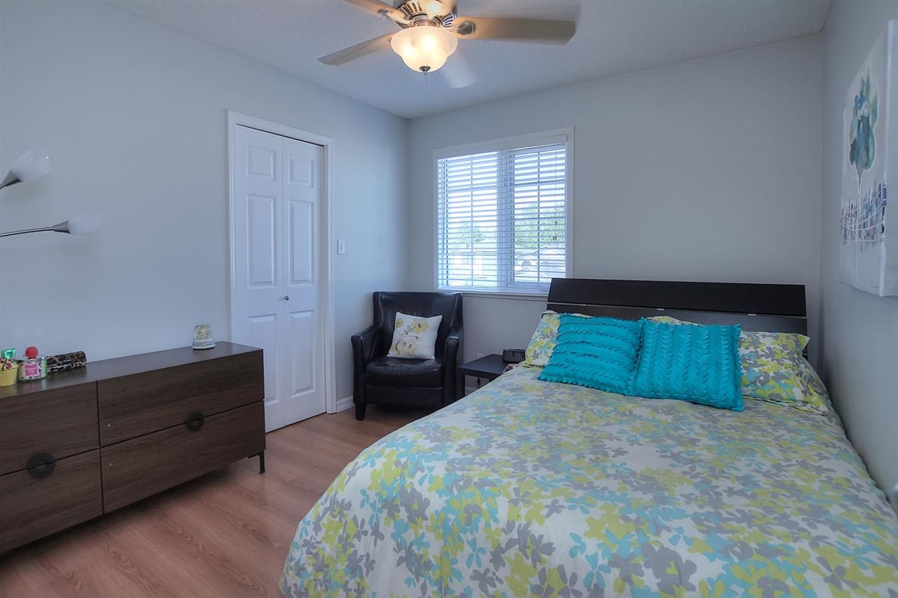 This bedroom has a walk in closet, laminate flooring, a ceiling fan and is right beside the main bathroom.