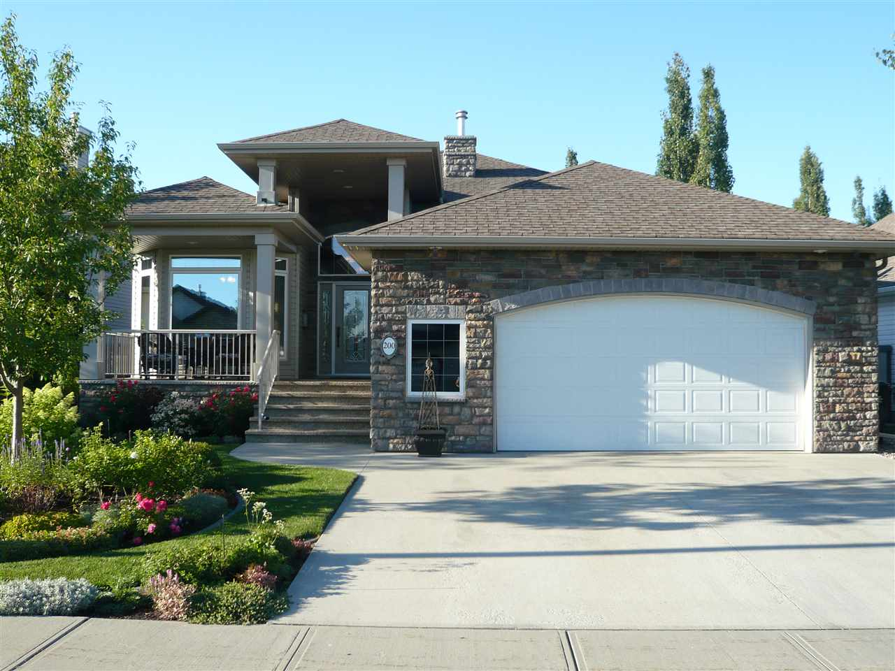 "If you can do it, you want to buy a home from these sellers!! Absolutely impeccable 1677 sq ft SANTOS Custom Built bungalow with over $200K in extras from the builder & likely over 100K in landscaping/yard. This home is a 1 bedroom plus den with an additional bedroom down. Lower level includes a rec room, wet bar & huge storage area currently used as a gaming room. The home has the best of everything, a stunning design & interior décor, it is spotless & has been maintained beautifully. Needs nothing! Exposed aggregate front porch, gorgeous stonework, 11'6"" ceiling in Living Rm, 9 ft ceiling in balance of home, amazing laundry room and walk thru pantry, gorgeous finishing/crown moulding, triple glazed windows on north and east side of home, impressive fireplace, steam shower in ensuite, composite decking, LED lighting and sprinkler system, much more! The HVAC system has furnace, radiant in-floor heating, an indirect hot water tank &  A/C. All this on a wonderful street on a large lot in Hawkstone Landing!!"