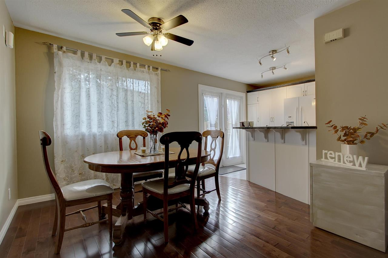 The dining room is very classy with the hardwood flooring and looks spacious as it opens to the newer white kitchen. There is also a built in desk area to the right of this photo.