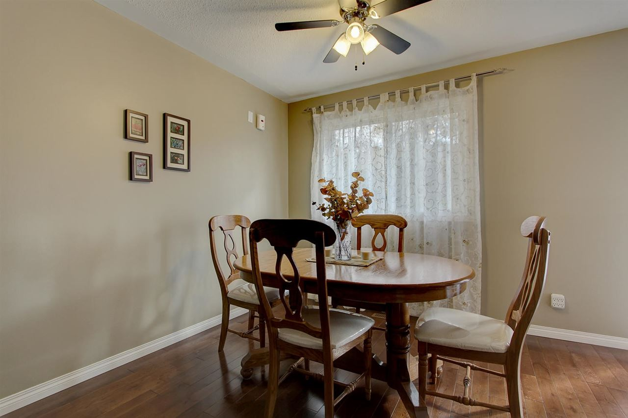 The dining room has a large window, ceiling fan and hardwood flooring which make the neutral paint look modern and up to date.