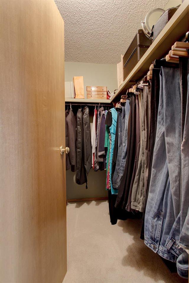 This walk in closet extends on the third wall behind the closet door. There is more than enough space to organize two wardrobes.