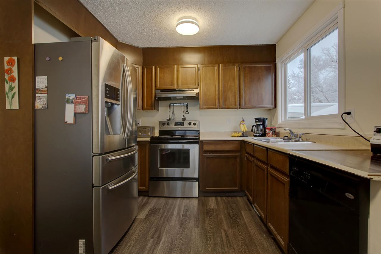 This efficient kitchen has a few nice stainless steel appliances. The maple cabinets would be very easy to paint out for an updated look. Note the large new window.