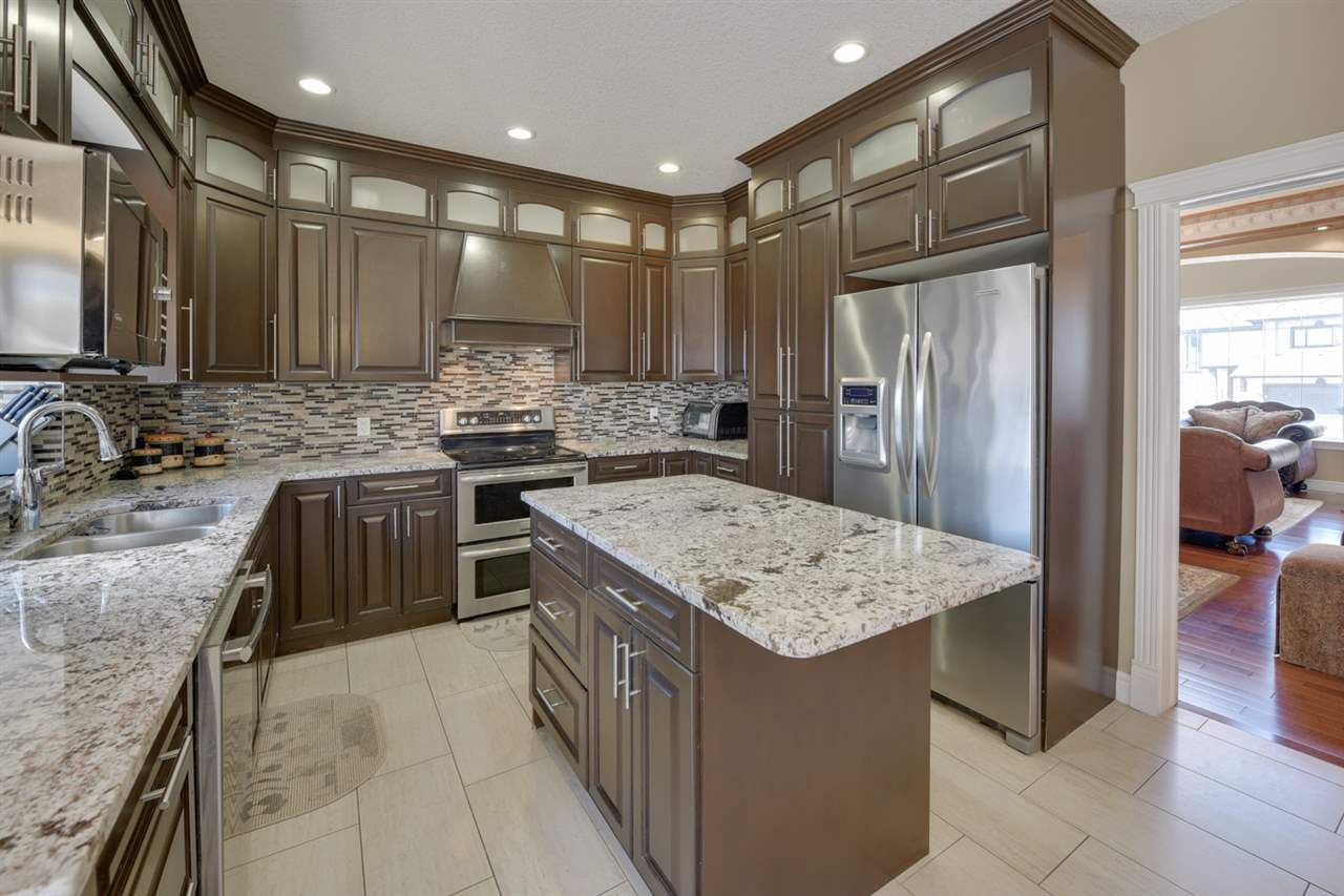 KITCHEN: Island kitchen with granite counters, mosaic backsplash, custom cabinets & top of the line appliances.