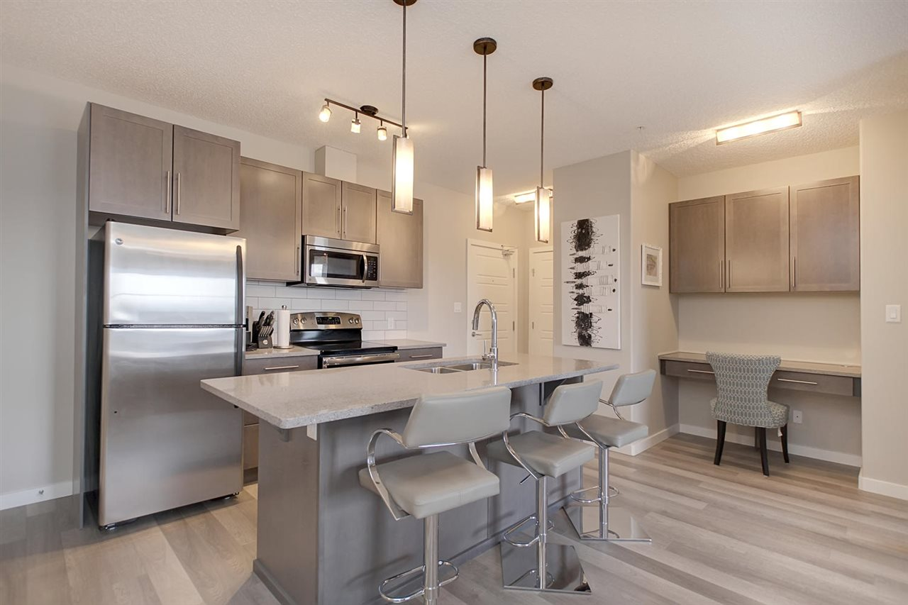 This view of the kitchen shows the layout well. Stainless steel appliances, the handy island with above lighting and the desk to the side make this efficient and good looking.