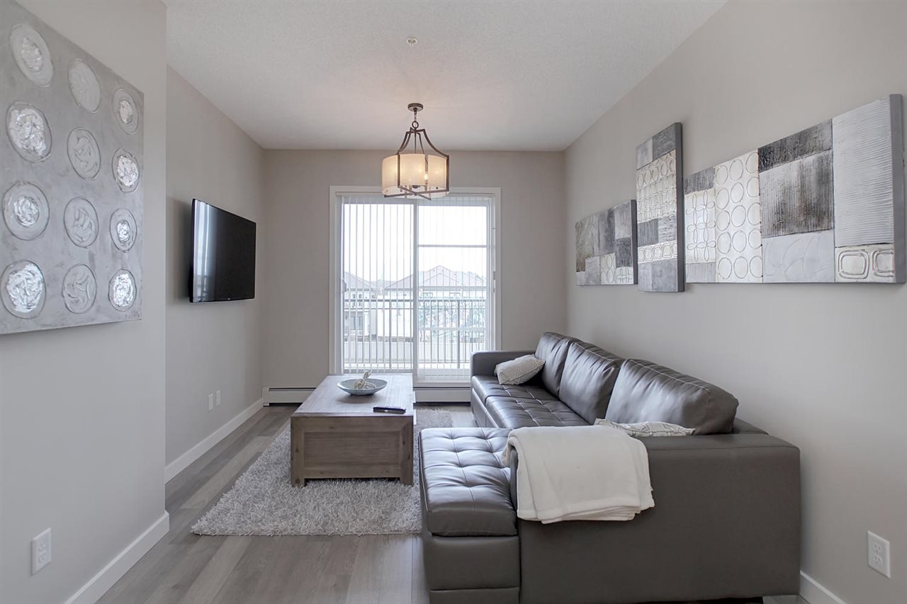 This living room space has a modern feel with the laminate flooring the wide patio doors leading to the balcony and the light which matches all the other new upgraded lighting in the unit.