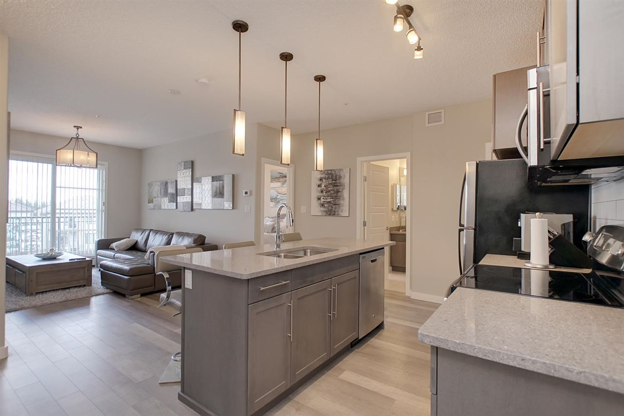 This is the view from the front door. Doesn't the unit have a modern and fresh feeling to it? The flooring makes the area flow nicely. The effect of the new lighting is visible in this photo. The quartz counter tops add a touch of expensive taste  to the unit.