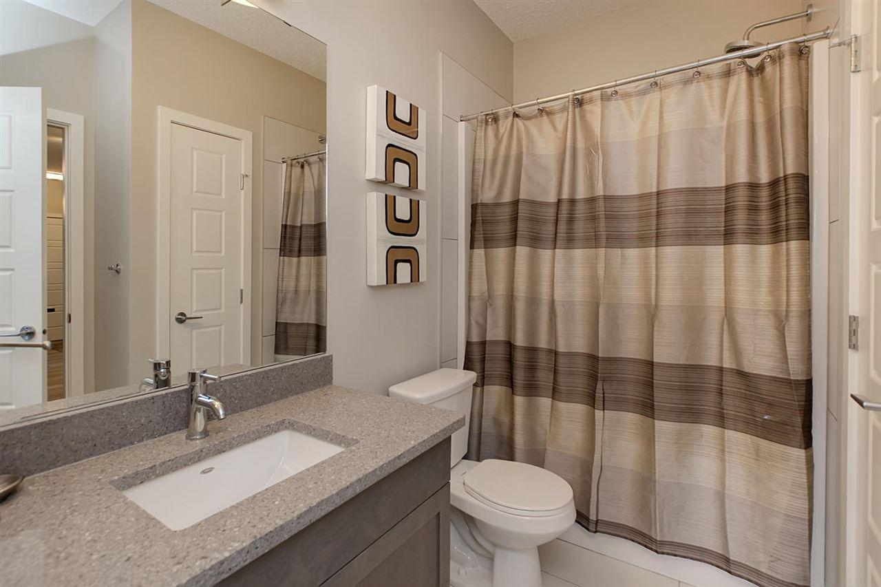 The main bathroom has the same quartz counter tops. This full four piece bath includes a deep soaker tub.