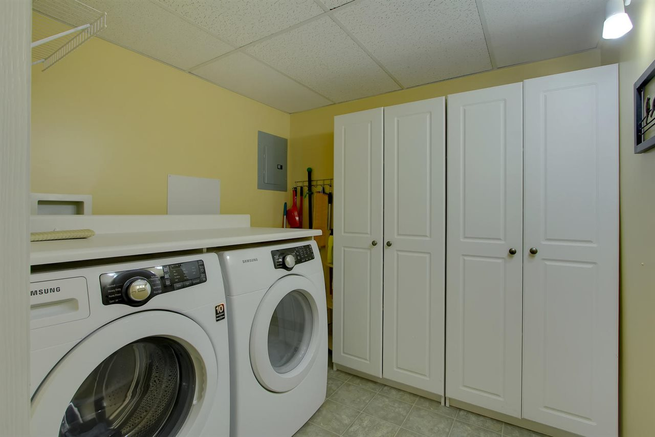 The laundry room has both full sized front loading washer and dryer and counter top above and Handy white pantry cabinets that will stay.